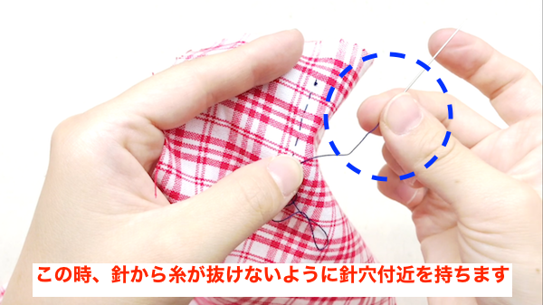 縫い針から糸が抜けないように縫いアナ付近を指で持っておく