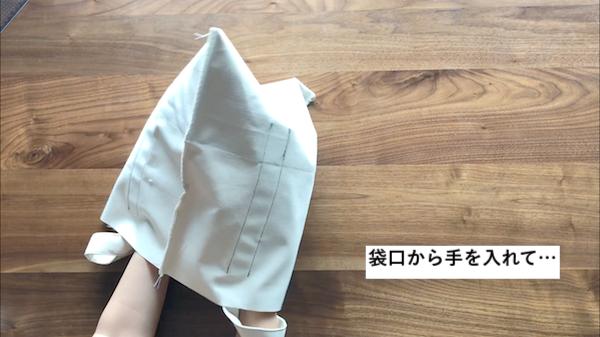 袋口から手を入れて布を広げる